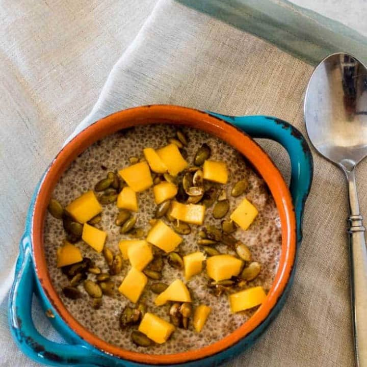 A turquoise and terracotta bowl with coconut chia breakfast pudding topped with candied pepitas and fresh mango on a linen napking with silver flatware.