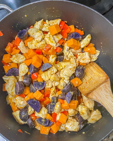 Chicken and vegetables in a saute pan with a wooden spoon being browned.