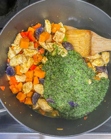 Cilantro puree added into the pot with the browned vegetables and chicken.