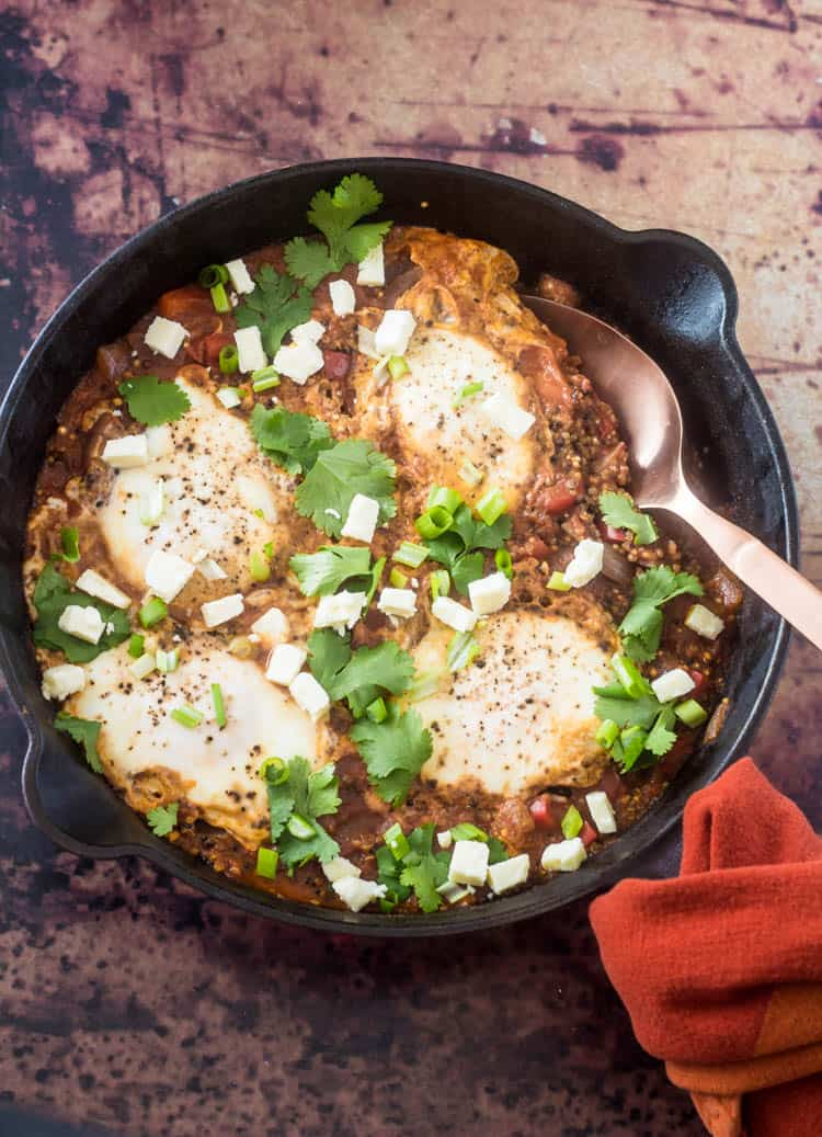 A cast iron skillet with the completed savory Peruvian quinoa breakfast bowls mixture with simmered eggs shakshuka style. Garnished with cilantro, scallion, and queso fresco.