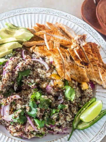 A round white platter with Mexican quinoa salad, grilled chicken breast, avocados.