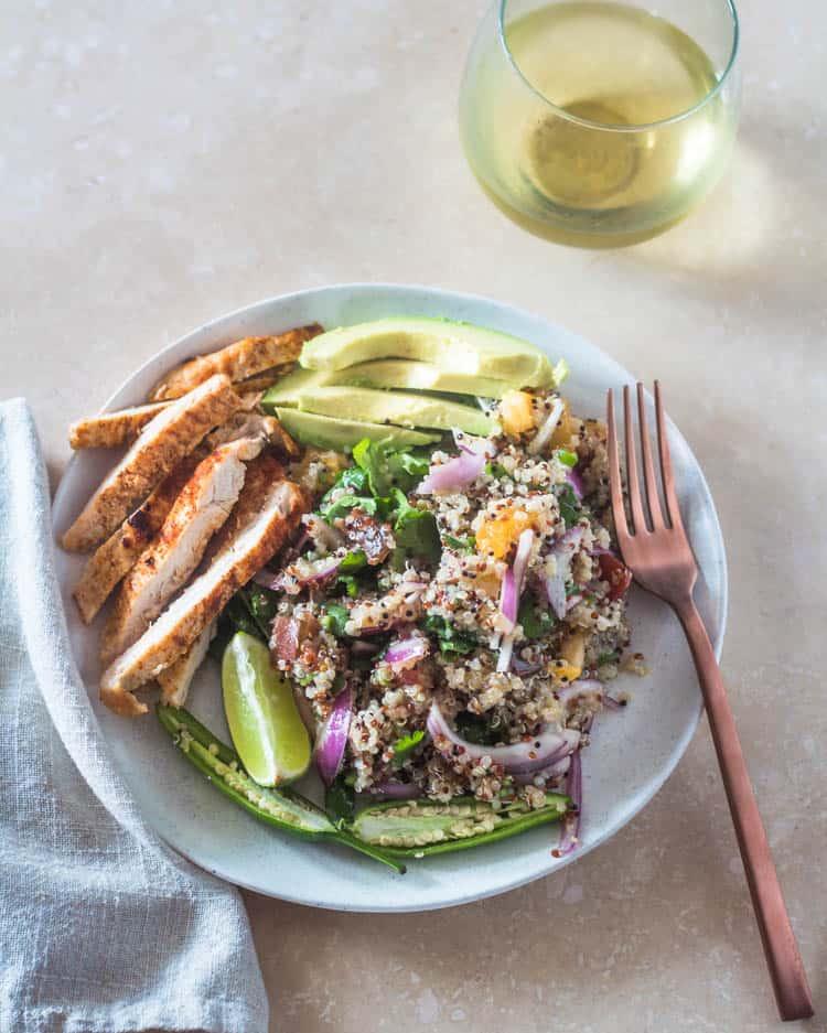 A single serving of quinoa a la Mexicana with sliced avocado, chicken breast, copper fork, glass of white wine.