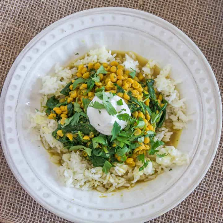 A white bowl of chana dal with spinach, rice, and yogurt.