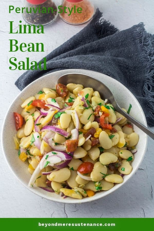 A white ceramic bowl of Peruvian lima bean salad with a grey napkin.