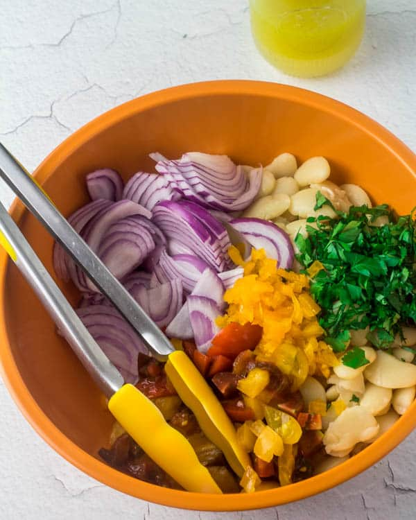 Lima bean salad ingredients in an orange bowl with tongs before combining.