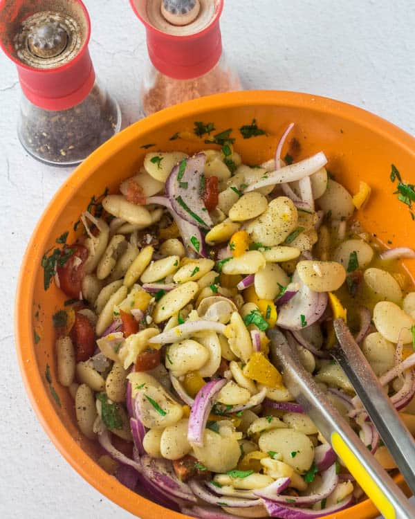 Lima bean salad tossed with the dressing in an orange bowl with salt and pepper grinders.