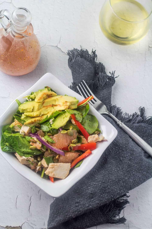 Yucatan chicken salad, a glass of wine, a bottle of chipotle citrus vinaigrette, a grey napkin, and flatware.