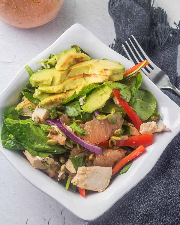 A white square bowl of Yucatan spinach salad with chipotle-citrus vinaigrett, a grey napkin, silver flatware.