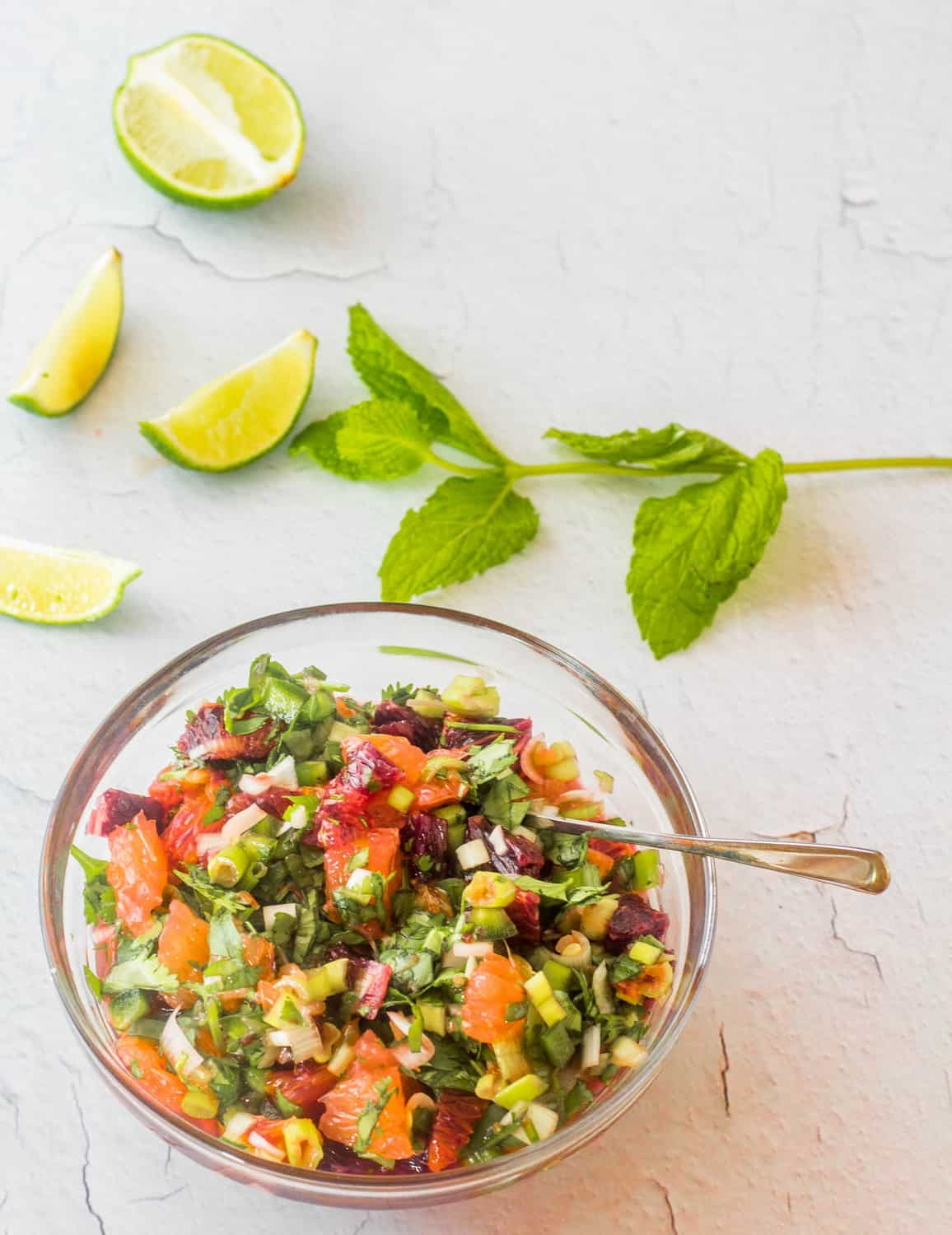 A glass bowl of Mexican citrus salsa with jalapeño, scallions, mint or cilantro alongside lime wedges and mint.