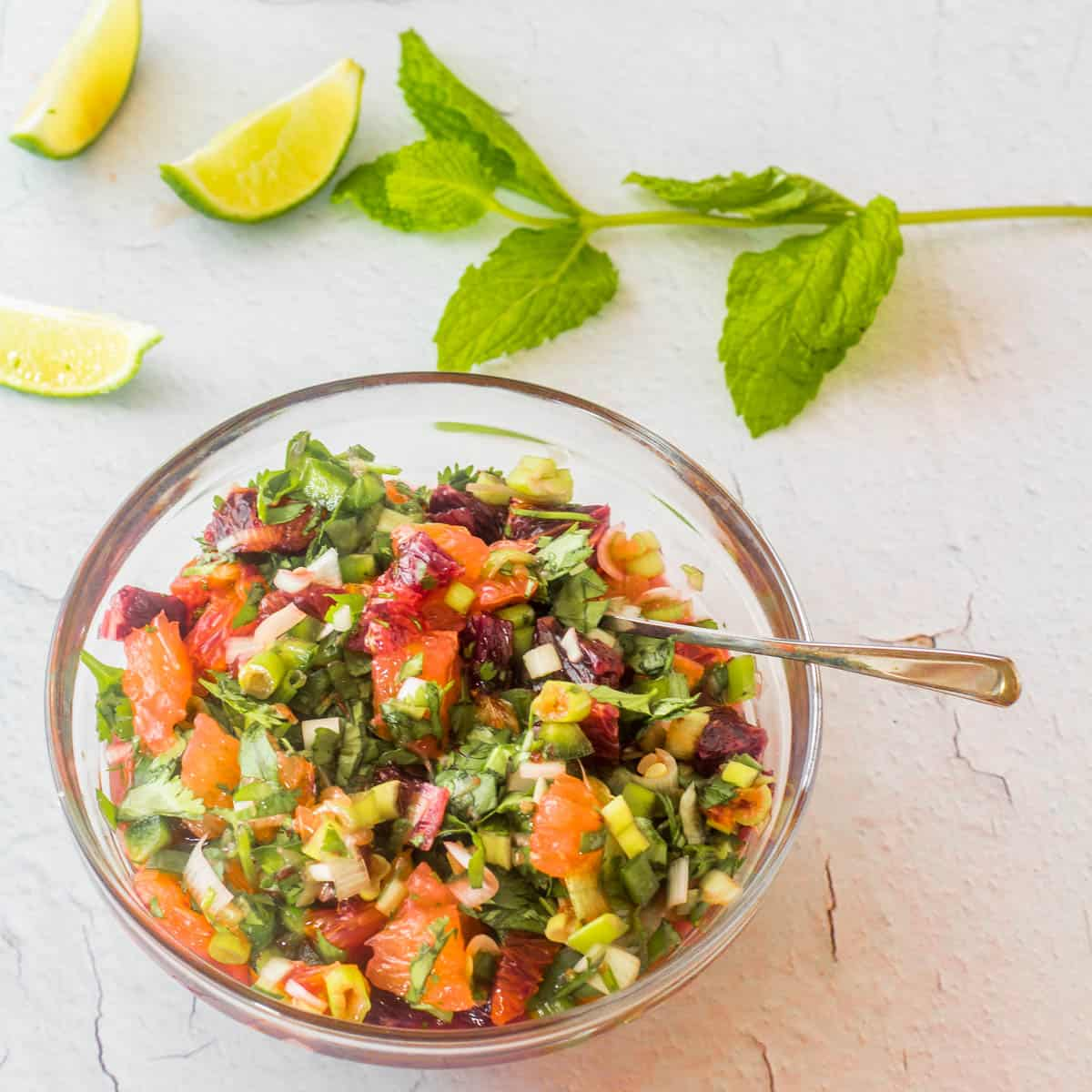 A glass bowl with cara cara and blood orange, lime, scallions, jalapenos, and cilantro with a tiny serving spoon.
