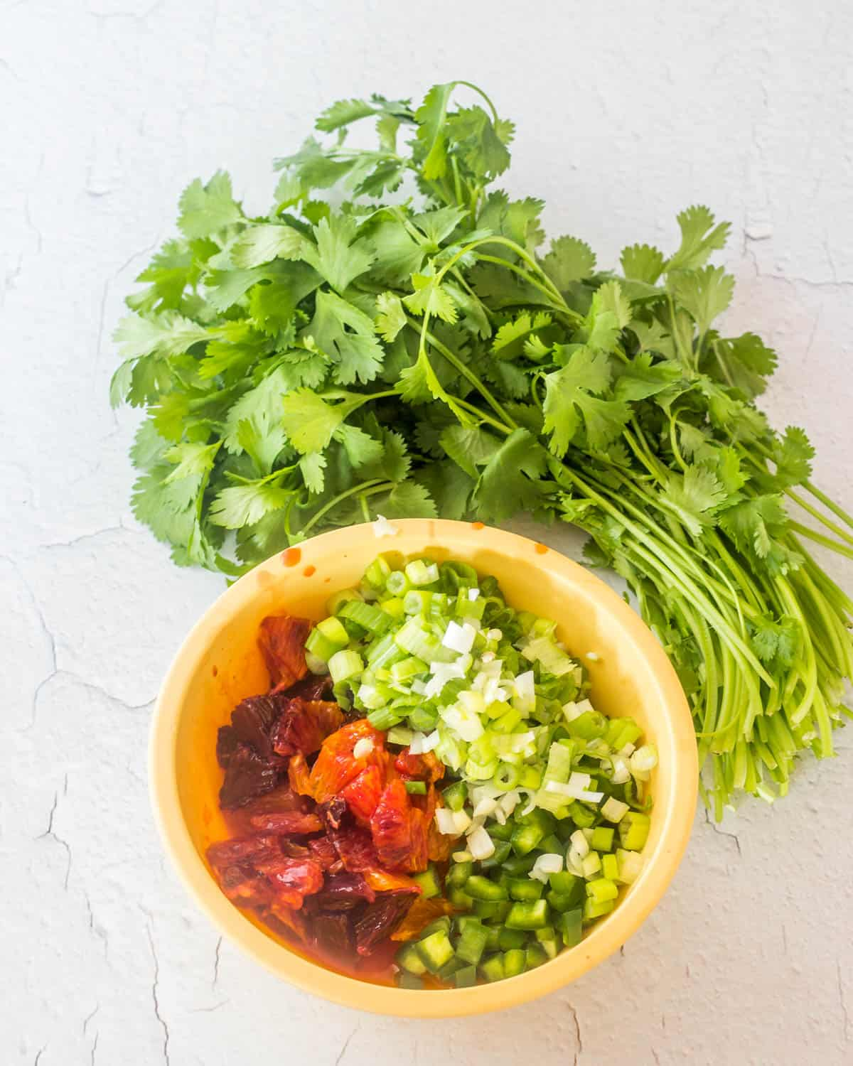 A yellow bowl of the prepared ingredients ready to finish the salsa.