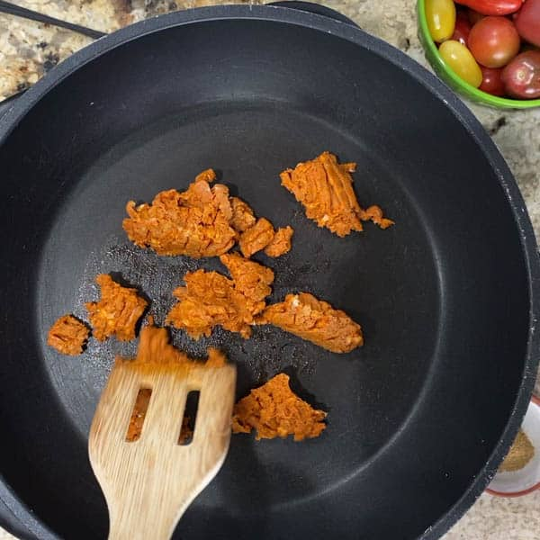 Chorizo frying in a pan with a wood spatula.