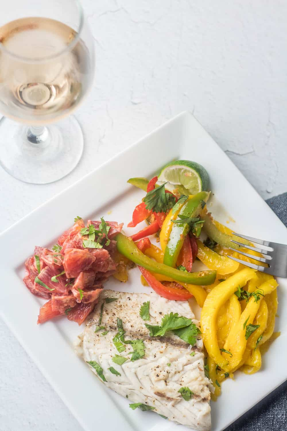 A bird's eye view of a square white plate with a Caribbean style fish fillet with caramelized mangoes, sautéed bell peppers, and orange salad.