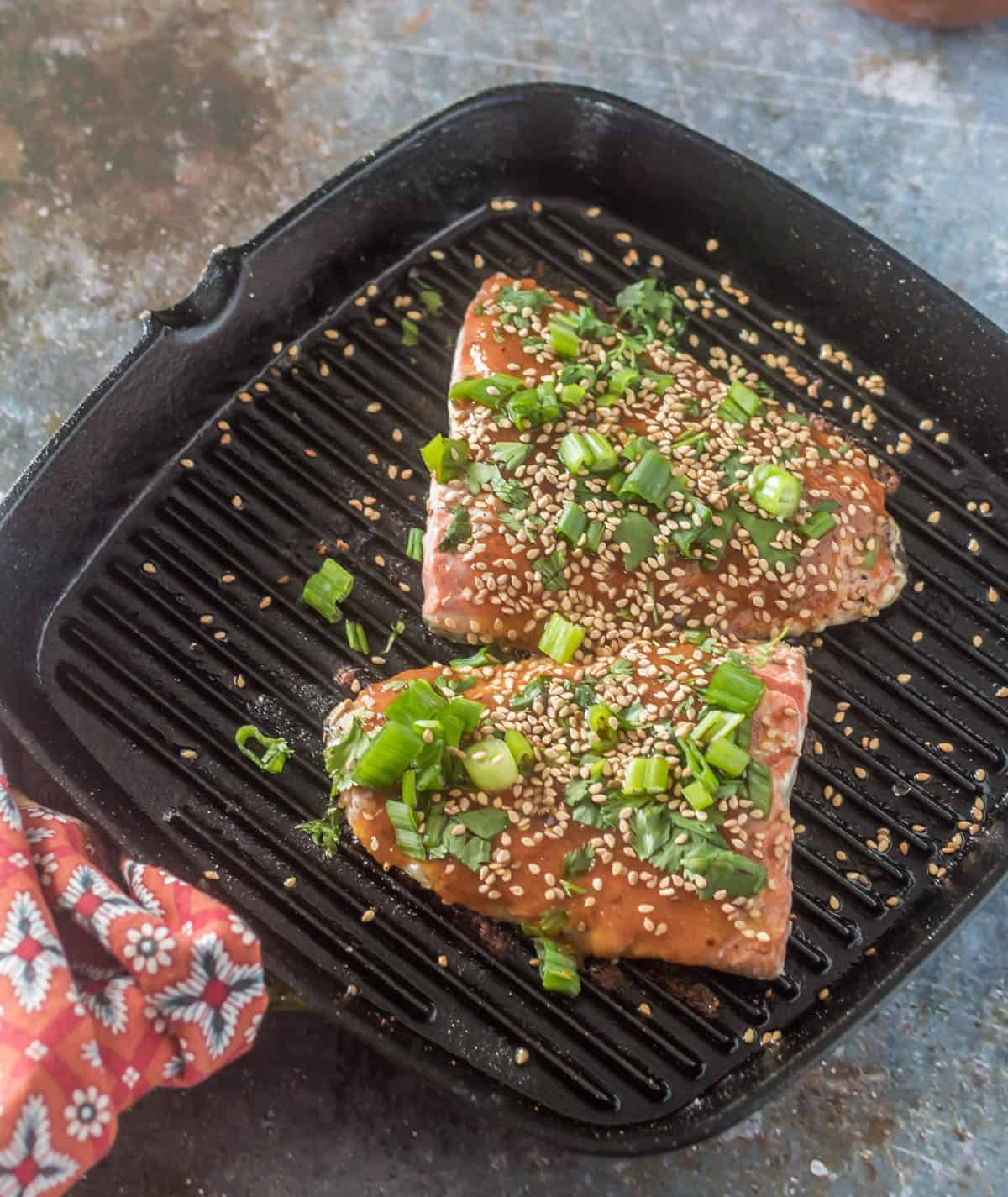 A griddle pan with 2 salmon portions glazed with homemade chamoy and sprinkled with sesame seeds, cilantro, and scallions.