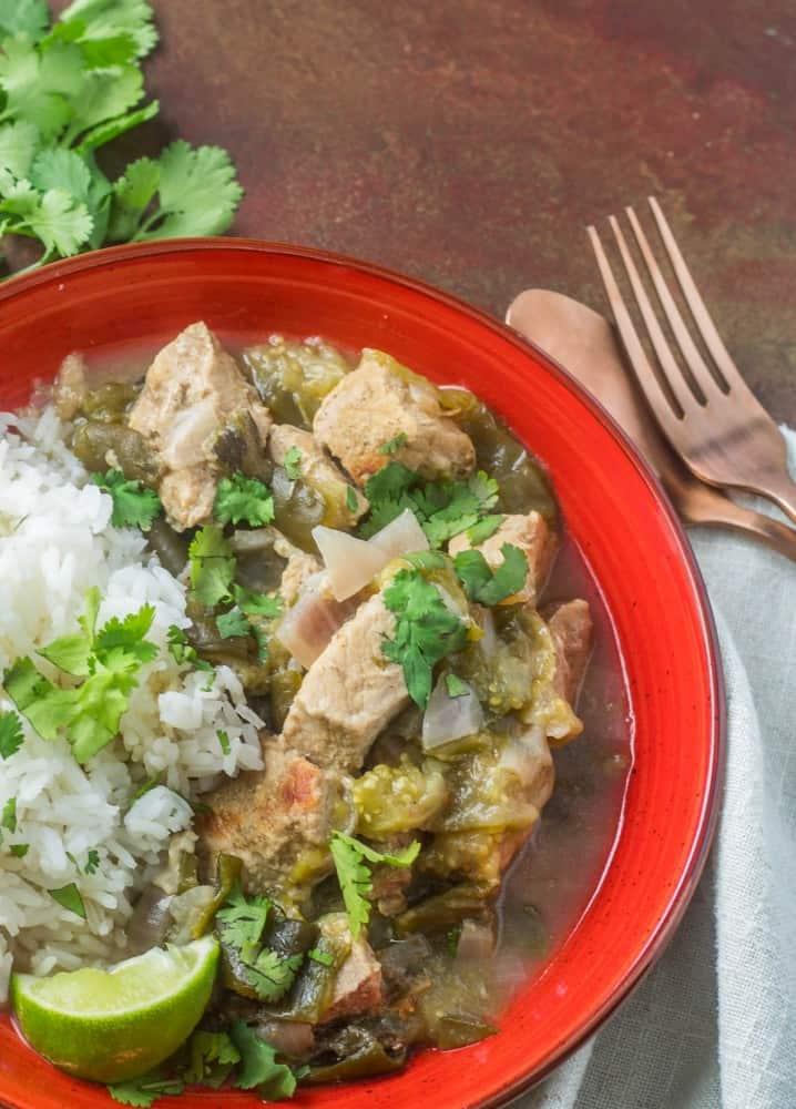 A red ceramic bowl with Instant Pot pork with tomatillos and green chile, white rice, lime wedge.