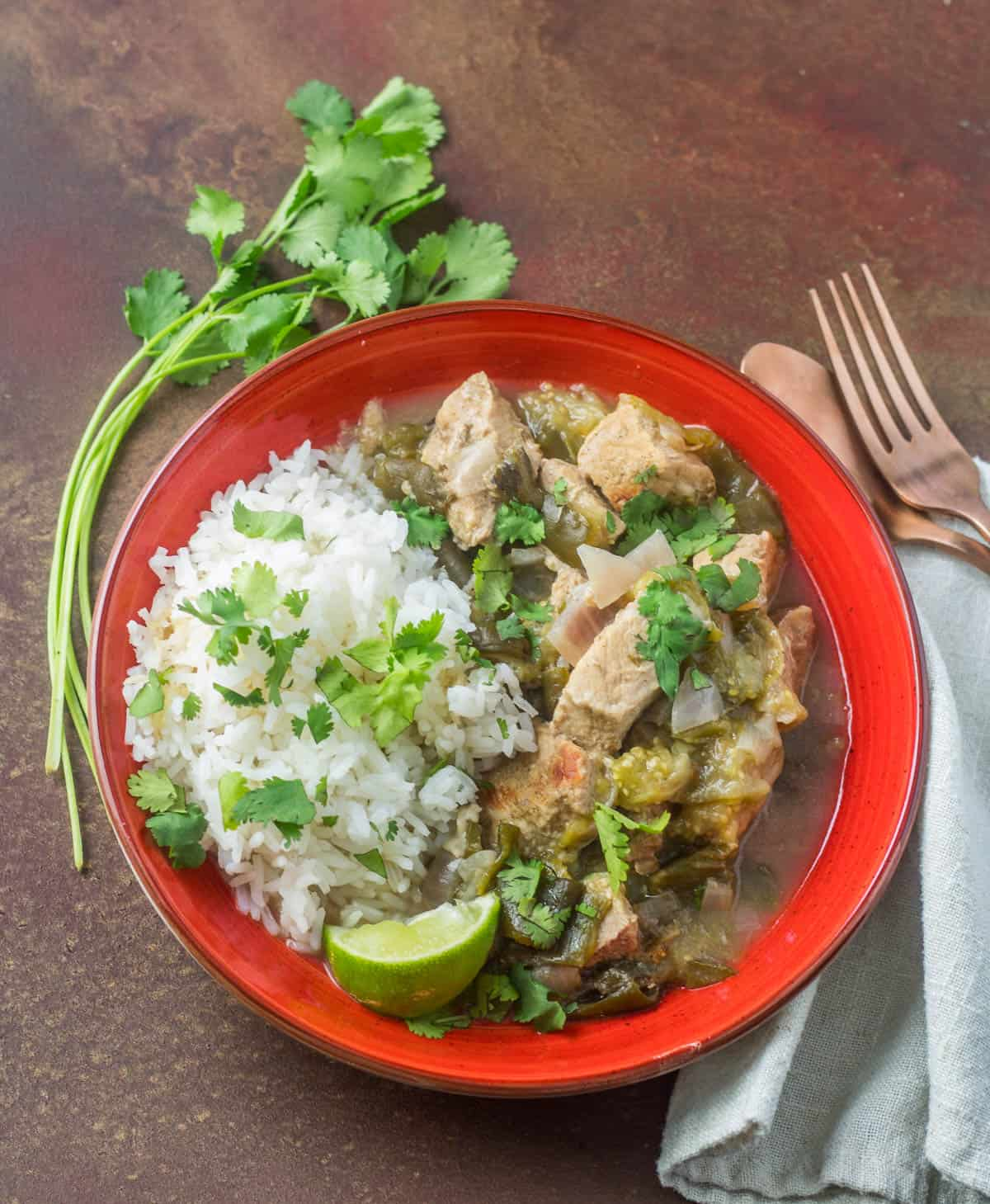 A red bowl of pork and rice garnished with cilantro and lime wedge alongside a big sprig of fresh cilantro, copper flatware and a linen napkin.