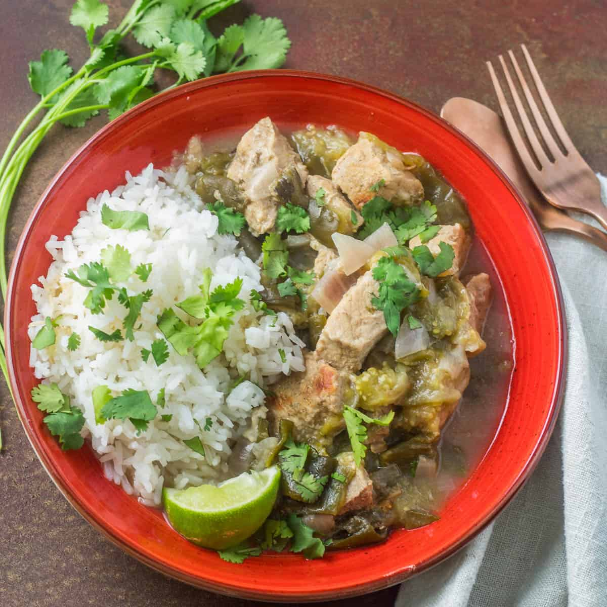 A red ceramic bowl of pork, tomatillos, green chile, and rice garnished with lime and cilantro.