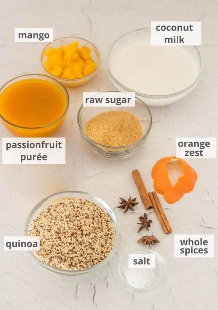 Ingredients for this quinoa dessert recipe in prep bowls - coconut milk and milk, orange zest, whole spices, salt, quinoa, raw sugar, passionfruit puree, and mango.