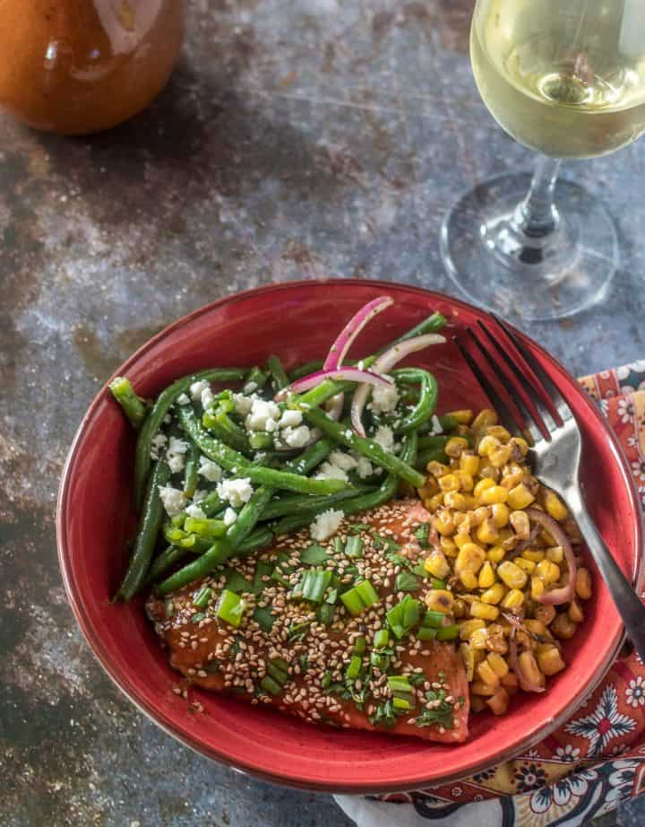 A red ceramic bowl with green beans salad, chamoy glazed salmon, and charred corn.