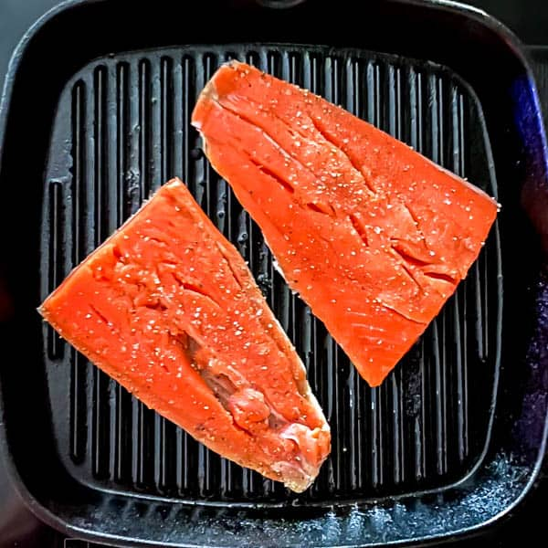 2 salmon portions skin side down on  a griddle.