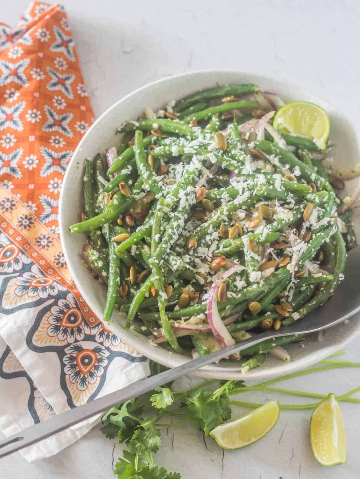 A white salad bowl of Mexican green beans salad with crumbled cotija, red onion, pepitas, and cilantro-lime dressing with a bright print napkin.