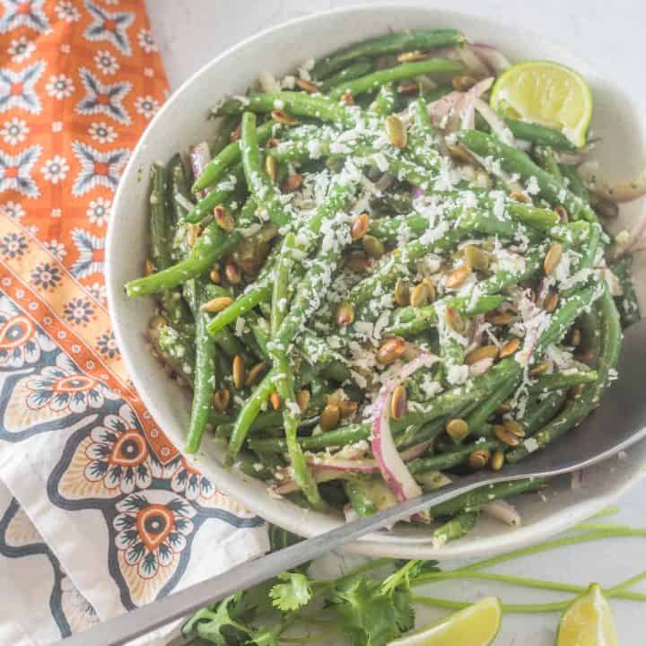 A white ceramic bowl of Mexican green bean salad with a bright print napkin and a silver spoon.