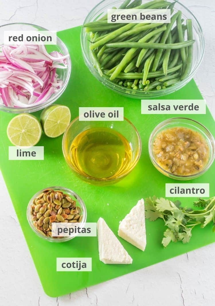 Ingredients for green bean salad: green beans, salsa verde, cilantro, cotija, pepitas, olive oil, lime, red onion.