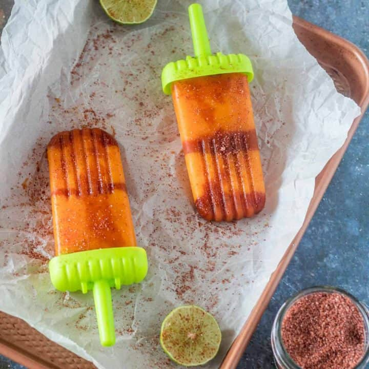 A copper tray with parchment and 2 boozy mangonada paletas, a lime wedge and tajin.
