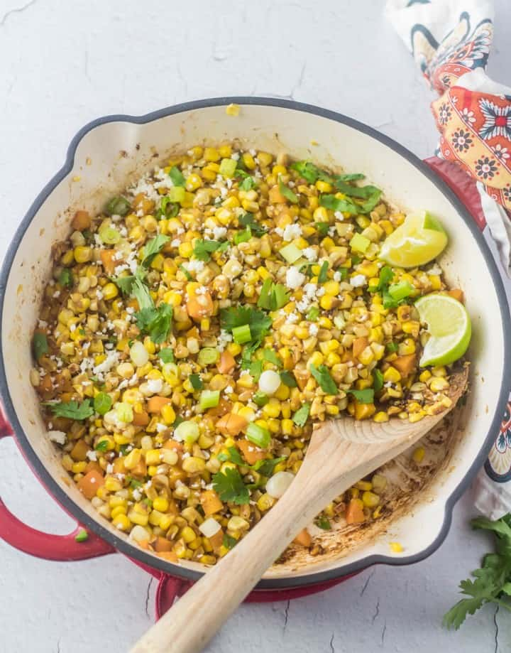 A red cast iron skillet with Mexican Charred Sweet Corn - a great Mexican side dish!