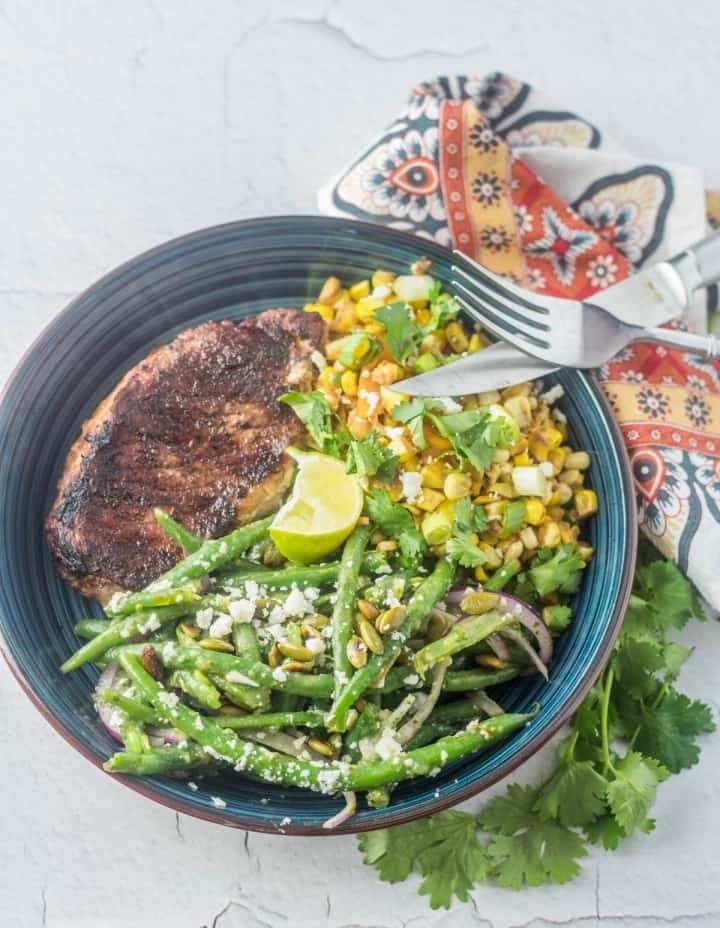 A blue shallow bowl with a tajin pork chop, skillet Mexican charred sweet corn, and Mexican green bean salad.
