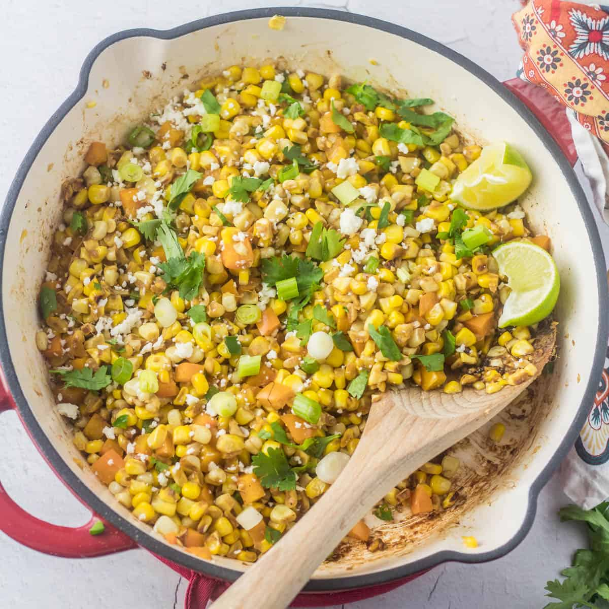 A red skillet with skillet Mexican charred sweet corn and a wooden spoon.