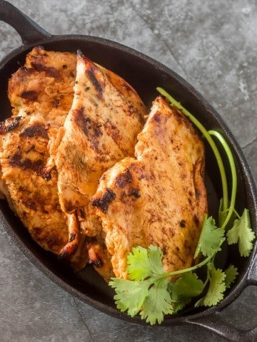 Grilled Tajín Chicken in a cast iron skillet with cilantro.