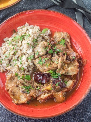 A red ceramic bowl with braised chicken and plums alongside herbed farro.