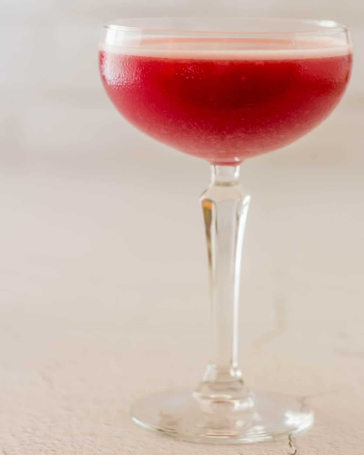 A close up of a coupe glass with gorgeous spiced plum pisco sour on a white background.