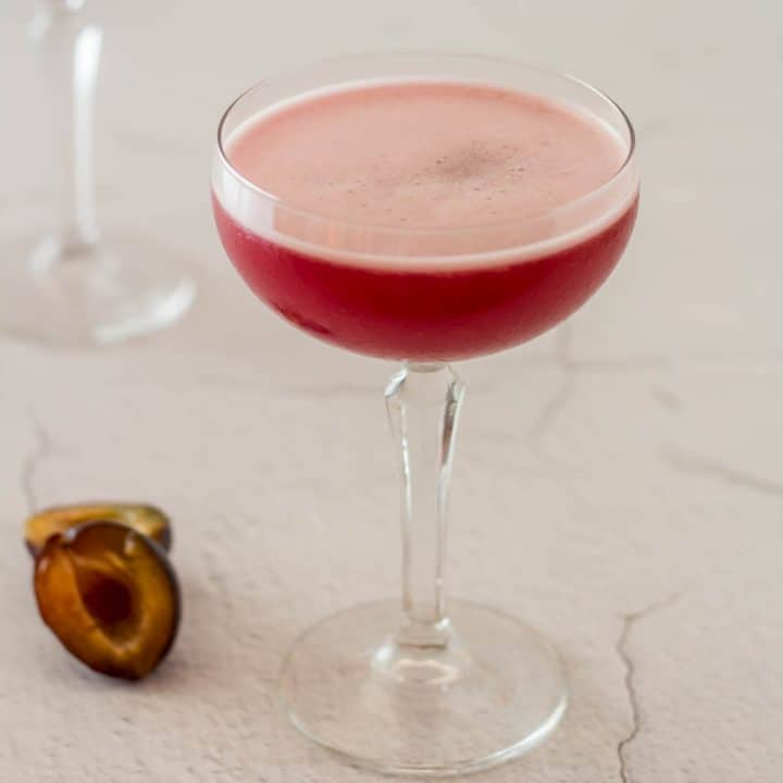 A single spiced plum pisco sour variant in a coupe glass next to a fresh plum.