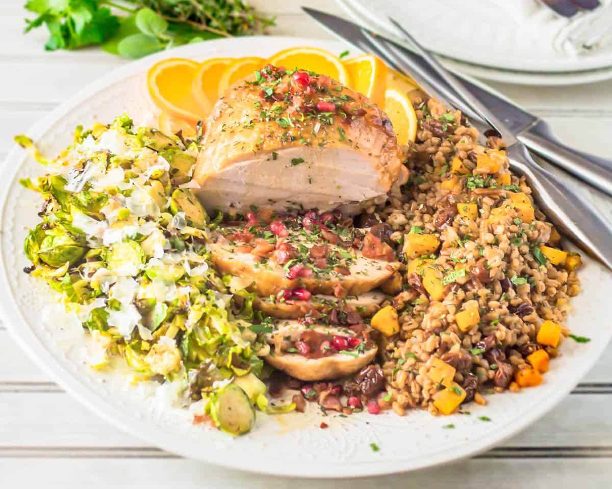 A large white ceramic platter with the entire small Thanksgiving menu - citrus brined turkey breast, roasted brussels, farro and butternut squash dressing.