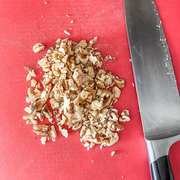 Coarsely chopped walnuts with a chef's knife on a red cutting board.