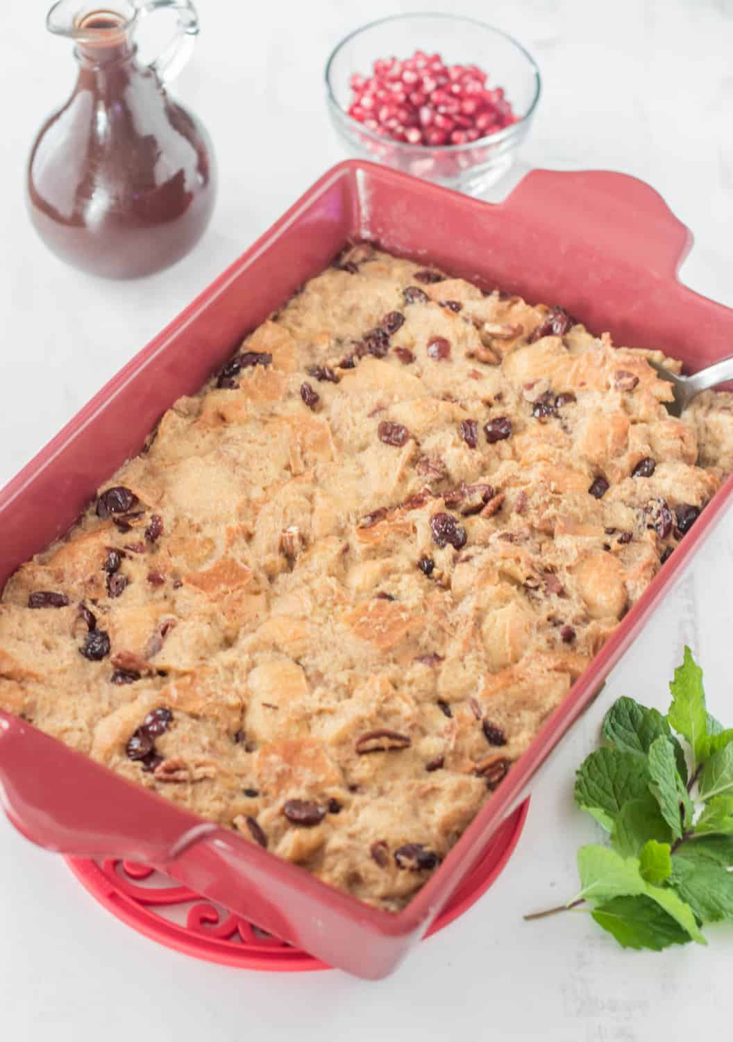 A red baking dish with the fully-cooked bread pudding alongside the  Mexican chocolate sauce and a mint sprig.