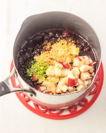 The cranberry sauce with the pears and zest added in a saucepan.