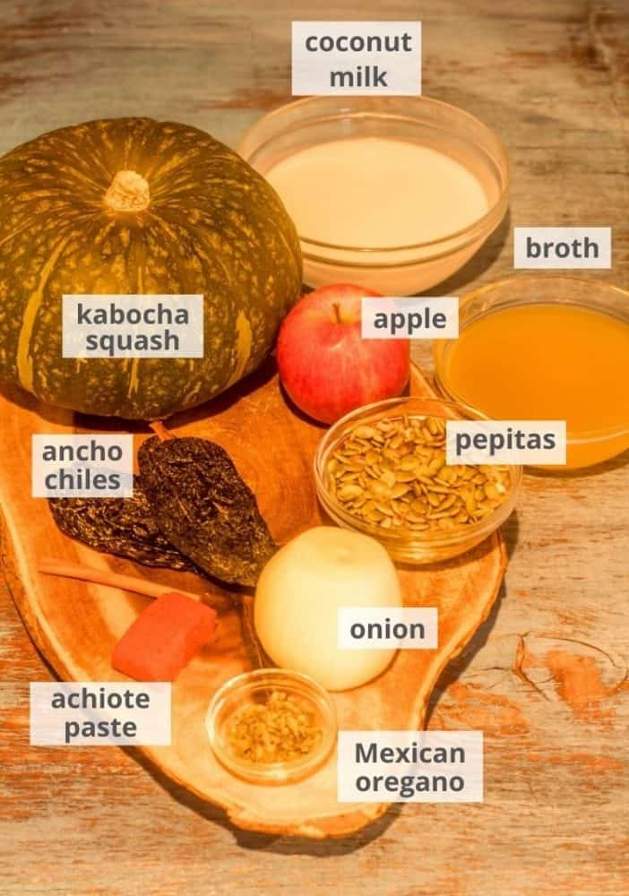 Ingredients for the kabocha squash soup including squash, apple, onion, spices, ancho chile, pepitas, on a wood cutting board.
