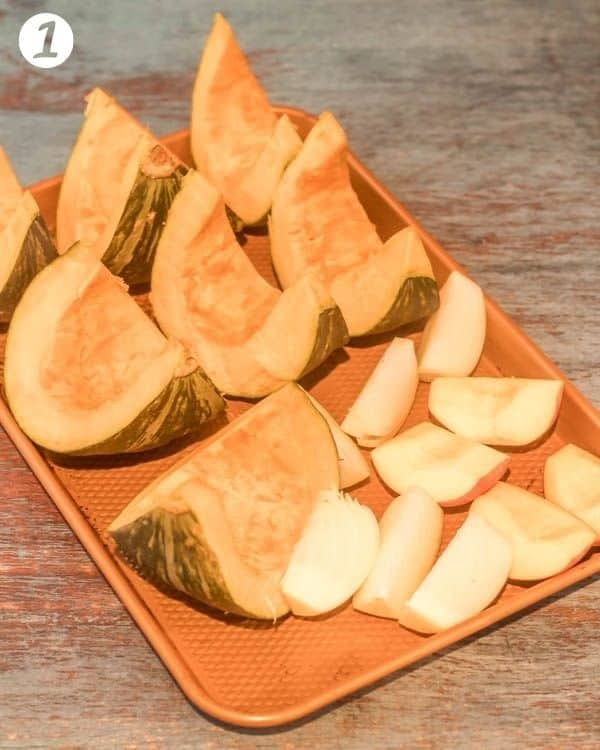 Kabocha squash wedges, apple wedges, and onion wedges on a copper baking sheet.