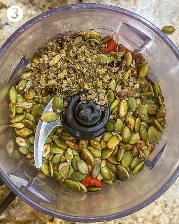 A food processor with ancho chiles, pepitas, achiote, Mexican oregano, and cinnamon prior to processing.