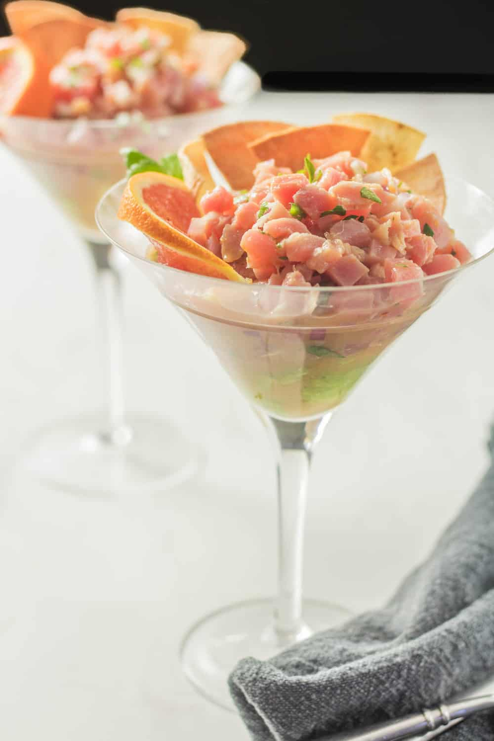 2 martini glasses filled with Latin Tuna Tartare and avocado garnished with cara cara oranges and air fryer corn tortilla chips.