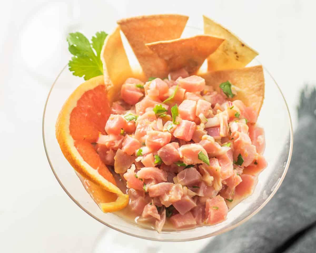 A close up bird's eye view of the Latin-inspired tuna tartare with cara cara orange slice and tortilla chips.