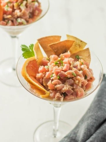 A martini glass with Latin-style tuna tartare with aji amarillo and citrus, atop avocado with tortilla chips.