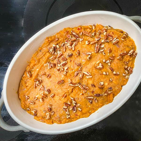 A white oval casserole dish with sweet potato mash ready to go in the oven.