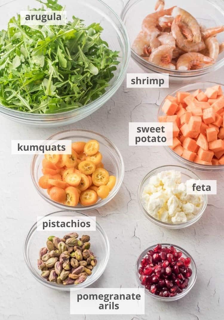 Blackened shrimp and arugula salad ingredients - shrimp, sweet potato, feta, pomegranate arils, pistachios, kumquats, arugula.