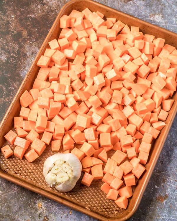 Cubed sweet potatoes and a bulb of garlic on a copper baking sheet before roasting.