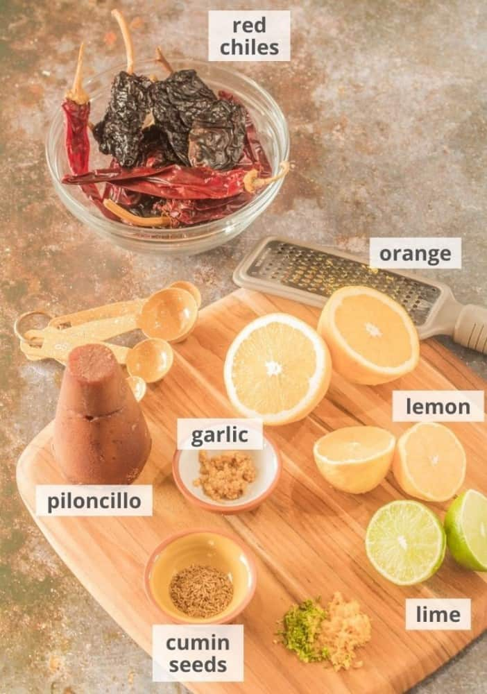 A cutting board with ingredients for the sous vide pork tenderloin marinade: Dried red chiles, lemon, orange, lime, cumin seeds, garlic, piloncillo.