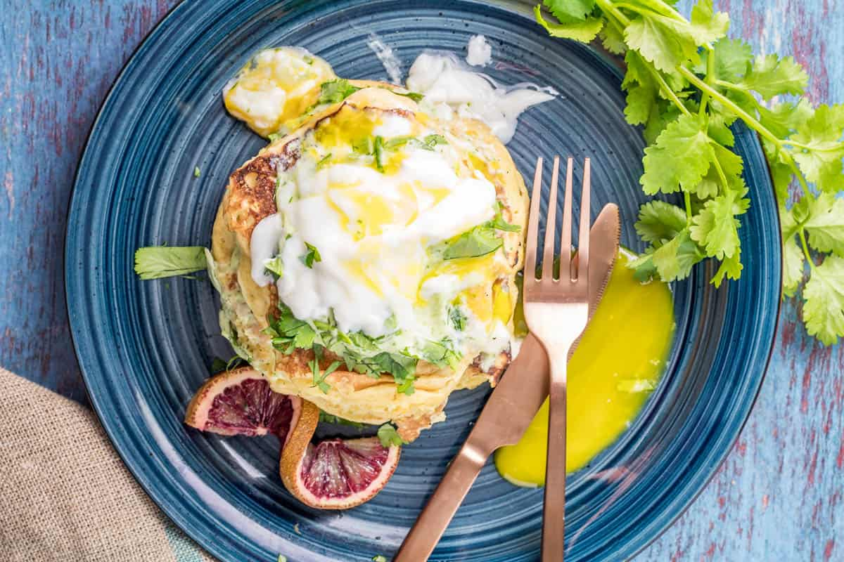 A blue ceramic plate with a stack of savory masa pancakes topped with avocado crema and a broken, runny poached egg.